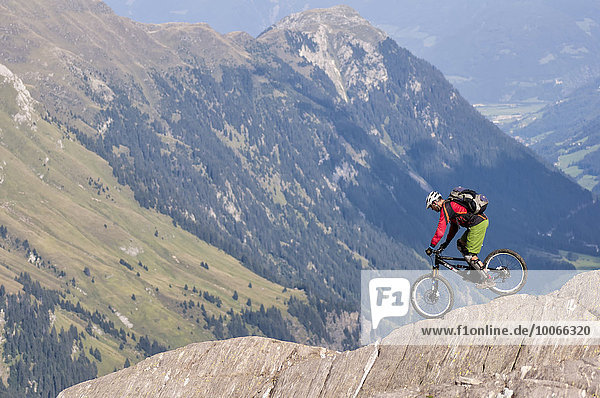 Freeride mountain biker with Liteville riding over cliff edge  Hohe Kreuzspitze  Racines  South Tyrol  Italy  Europe