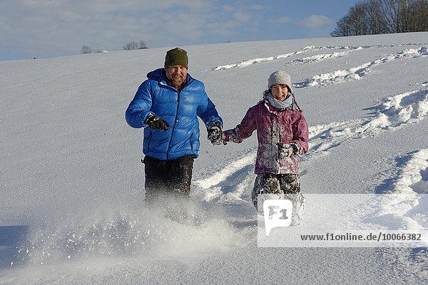 Vater und Tochter laufen im tiefen Schnee  Bad Heilbrunn  Oberbayern  Bayern  Deutschland  Europa