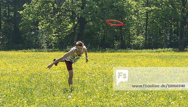 Junger Mann wirft Frisbee  gelbe Blumenwiese  Perlacher Forst  München  Bayern  Deutschland  Europa