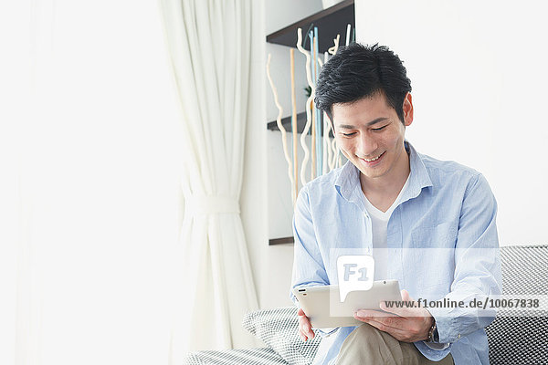 Japanese young man on the sofa with tablet