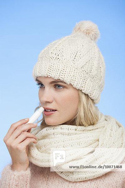 Eine Frau, die Lippenbalsam auf ihre Lippen aufträgt.