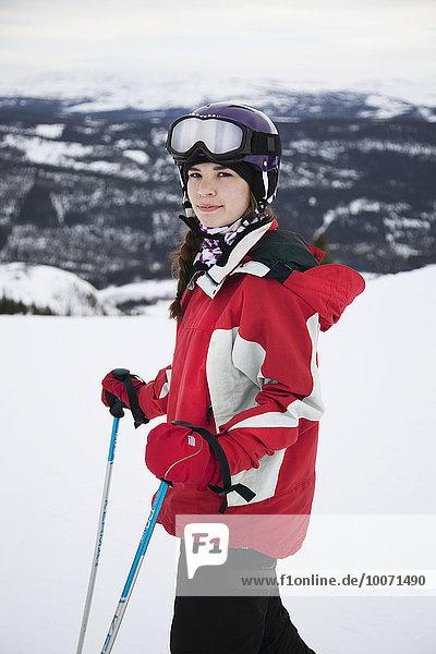 Porträt einer selbstbewussten jungen Frau in Skikleidung am Berg