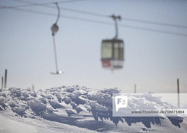 Schneebedeckter Berg mit Luftseilbahn im Hintergrund