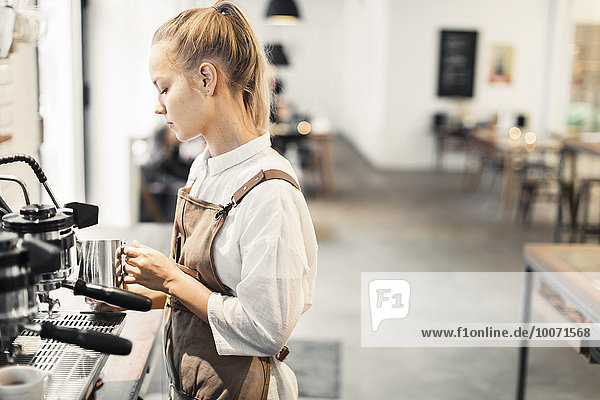 Junge Barista mit Espressomaschine im Café