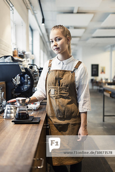 Portrait of confident female barista standing at counter in coffee shop