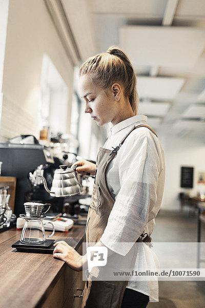 Seitenansicht der jungen Barista  die am Tresen Kaffee kocht