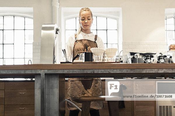 Barista arbeitet an der Theke im Coffee Shop