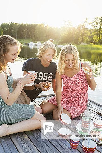 Glückliche Freunde beim Frühstück am Pier am See