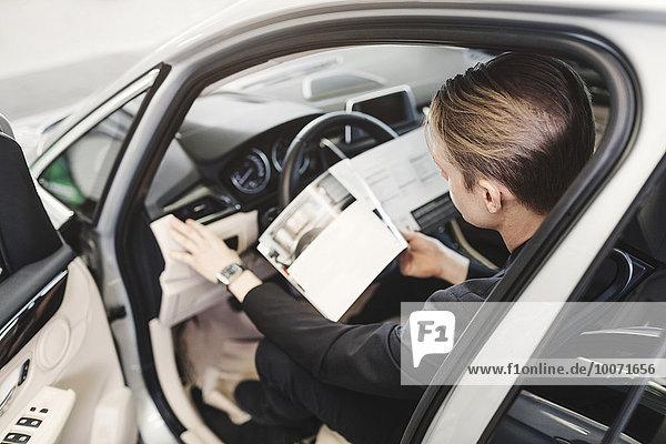 Großer Blickwinkel auf den Mann  der die Broschüre liest  während er im Auto sitzt.