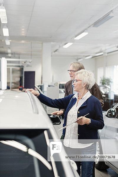 Seniorenpaar  das das Auto im Ausstellungsraum untersucht