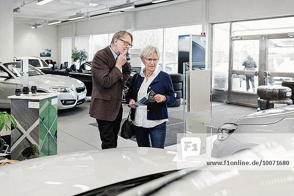 Seniorenpaar diskutiert über das Auto im Laden