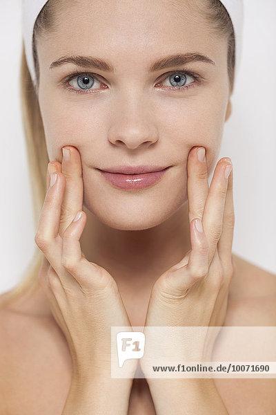 Schöne Frau  die Feuchtigkeitscreme auf ihr Gesicht aufträgt.