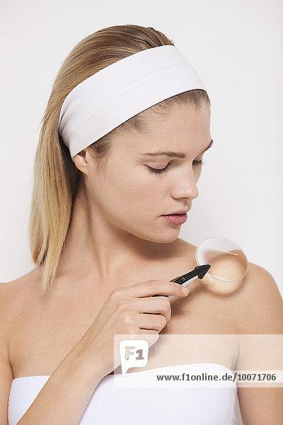 Schöne Frau untersucht ihre Haut mit Lupe
