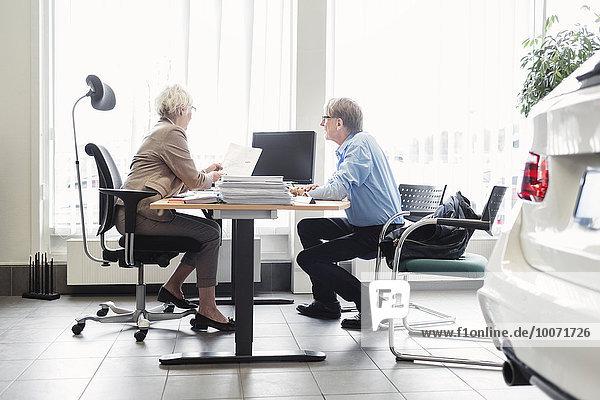 Verkäuferin erklärt dem Mann im Autohaus Dokumente am Schreibtisch