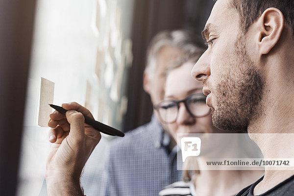 Seitenansicht des Geschäftsmannes beim Schreiben auf Klebezettel im Büro