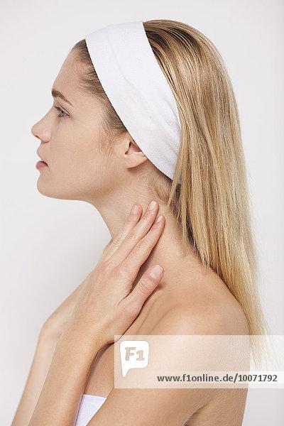 Schöne Frau mit Feuchtigkeitscreme am Hals