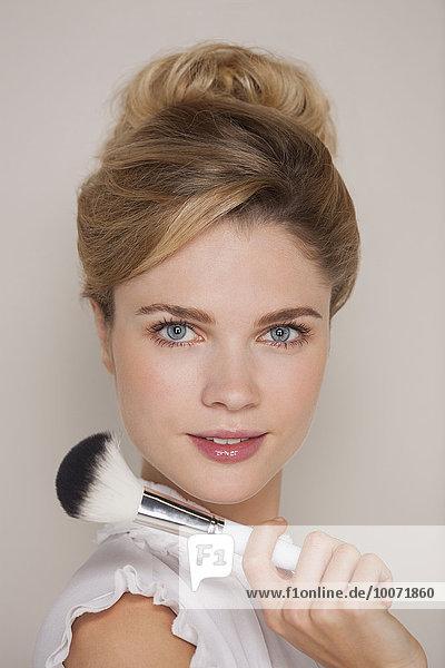 Porträt einer schönen Frau mit Schminkpinsel