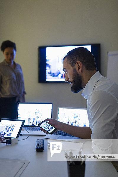 Geschäftsmann  der mit Kollegen im Büro Technologien einsetzt