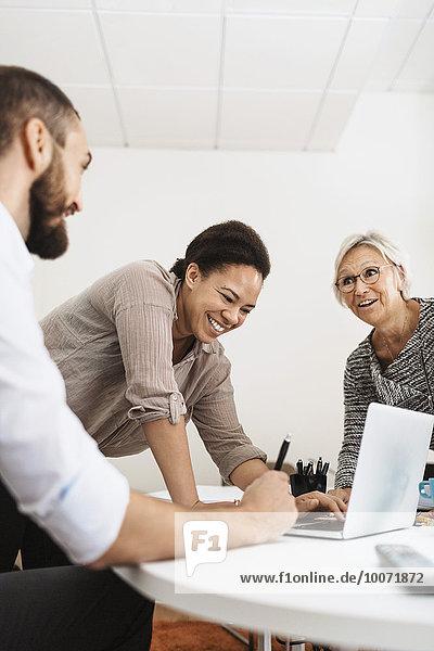 Glückliche Geschäftsleute mit Laptop im Büro