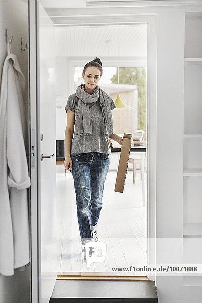 Volle Länge der Architektin  die zu Hause auf die Tür zugeht.