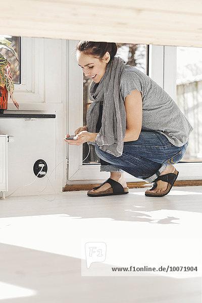 Seitenansicht der Frau  die das Handy mit dem Ladegerät zu Hause verbindet