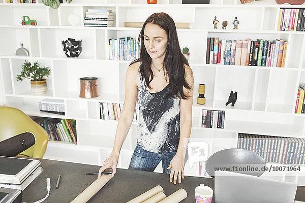 Architektin steht am Tisch im Home-Office