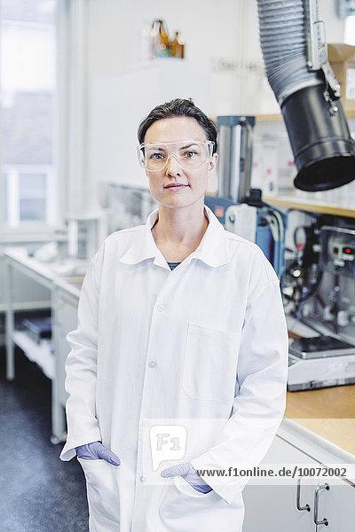 Porträt einer selbstbewussten Wissenschaftlerin mit den Händen in der Tasche im Labor