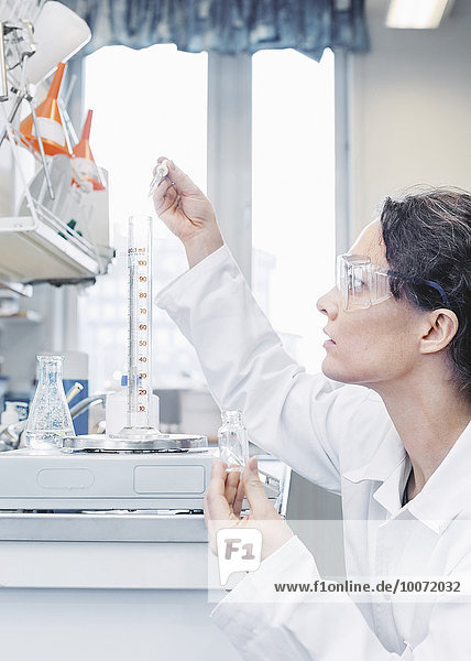 Female scientist pouring chemical in beaker at laboratory