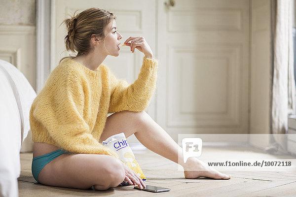 Frau  die Telefon benutzt und Chips isst