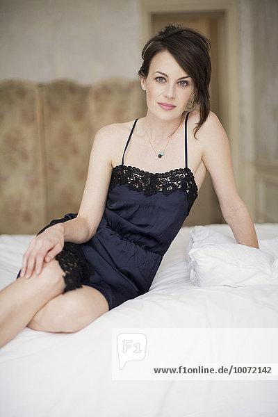 Porträt einer schönen Frau auf dem Bett sitzend