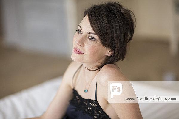 Schöne Frau auf dem Bett sitzend