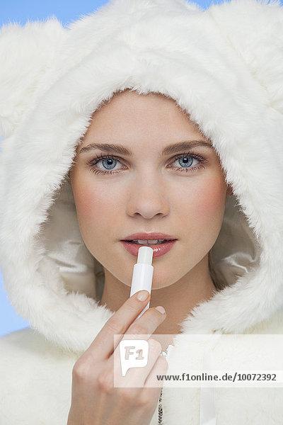 Eine Frau  die Lippenbalsam auf ihre Lippen aufträgt.