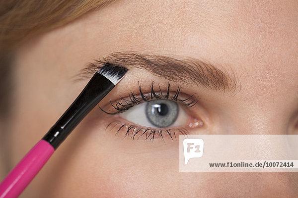 Schöne Frau bürstet Augenbraue