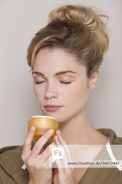 Beautiful woman smelling cream