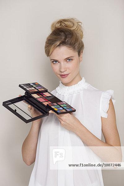 Beautiful woman holding eye shadow palette