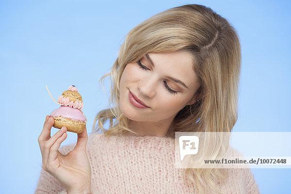 Nahaufnahme einer schönen Frau  die eine französische Erdbeerreligieuse hält.