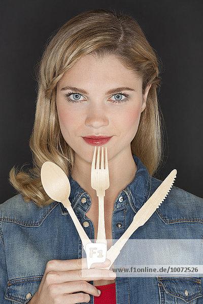 Porträt einer schönen Frau mit Küchenutensilien