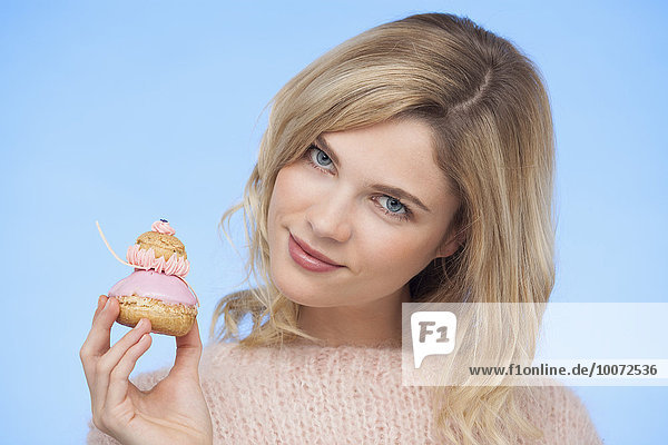Portrait of a beautiful woman holding a french strawberry religieuse