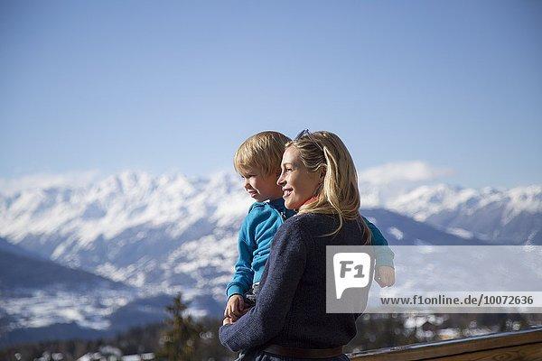Frau trägt ihren Sohn mit schneebedecktem Berg im Hintergrund  Crans-Montana  Schweizer Alpen  Schweiz