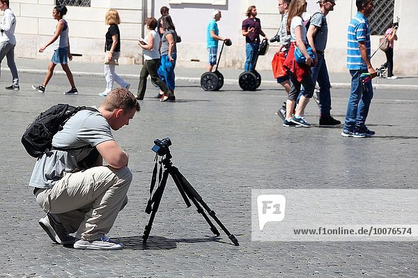 Tourist with tripod taking photograph in piazza navona square in Rome  Italy