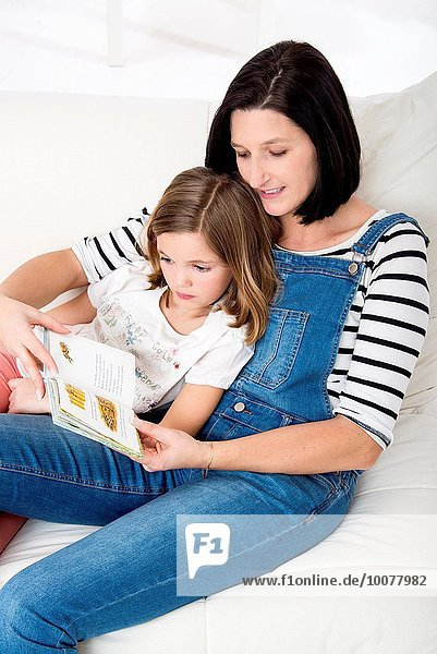 Little girl sitting on her mother´s lap  and reading a book in her bedroom