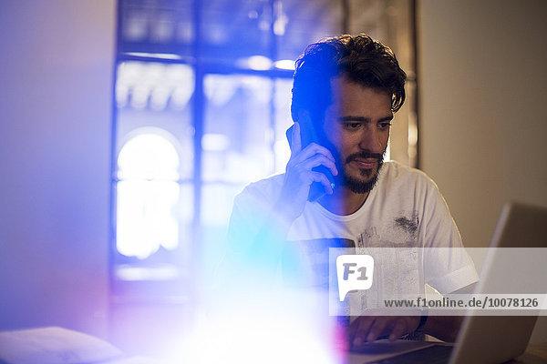 Casual Geschäftsmann im Gespräch auf dem Handy am Laptop