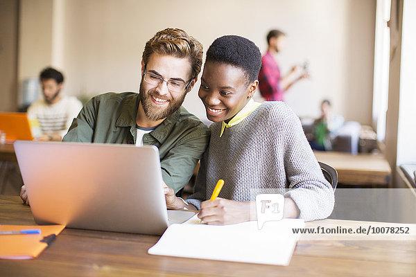 Lächelnde kreative Geschäftsleute mit Laptop und Brainstorming