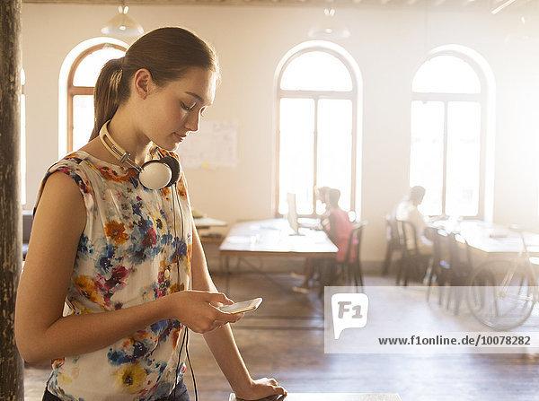 Lässige Geschäftsfrau mit Kopfhörer SMS mit Handy im sonnigen Büro