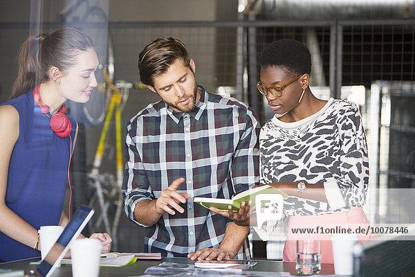 Kreative Geschäftsleute  die das Buch im Meeting anschauen