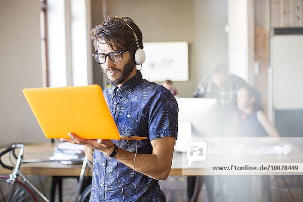 benutzen,Notebook,Geschäftsmann,Freizeitbekleidung,Kopfhörer,Büro,Kleidung