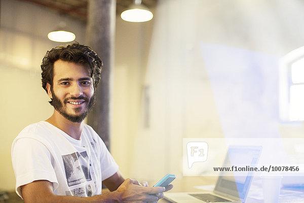 Portrait lächelnden Geschäftsmann SMS auf dem Handy am Laptop