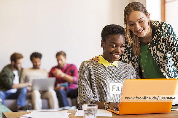 Lächelnde kreative Geschäftsfrauen bei der Arbeit am Laptop im Büro