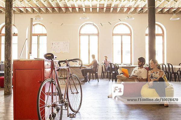 Kreative Geschäftsleute mit Laptop auf Bohnensäckchenstühlen im Büro