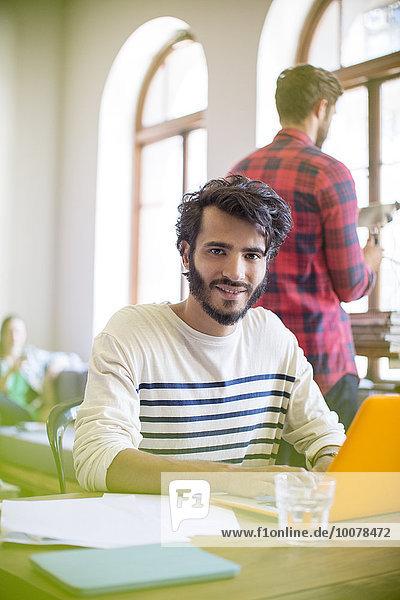 Porträt selbstbewusster Geschäftsmann mit Laptop im Büro